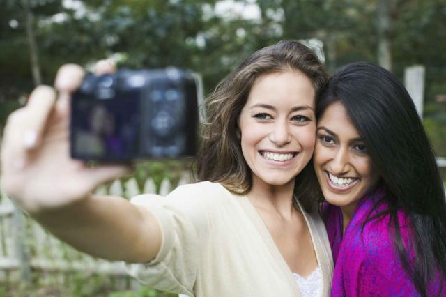 Two women taking picture of themselves with a digital camera