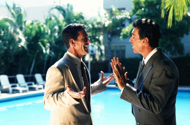 Businessmen arguing by swimming pool