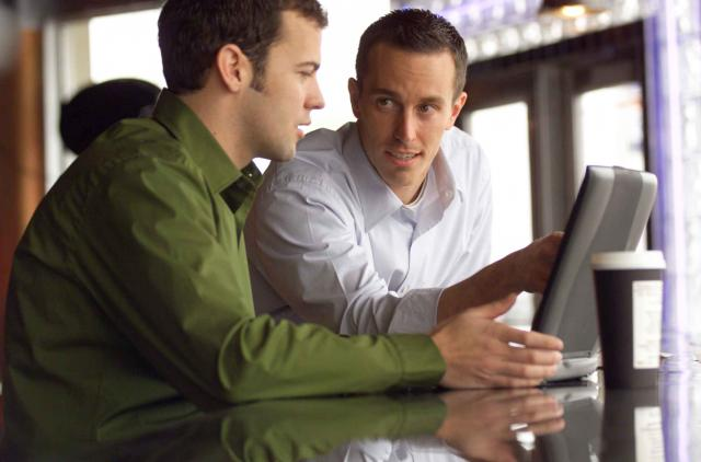 lifestyle photo of two caucasian male friends as they sit and talk around a laptop computer