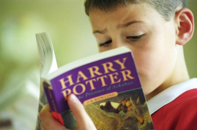 A young boy reads �Harry Potter and the Prisoner of Azkaban� by J.K. Rowling in a book shop in Shirley, Birmingham, U.K.