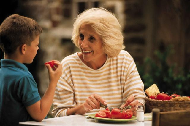 Grandmother with grandson while cutting tomatoes