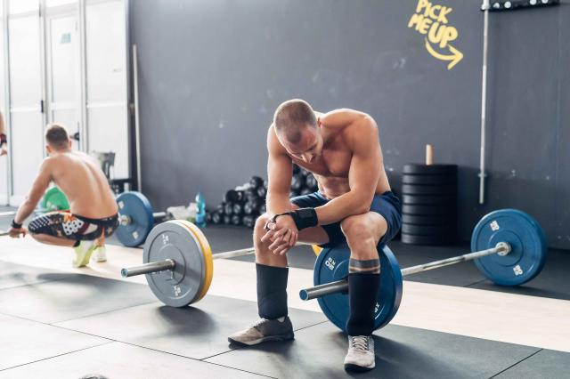 Exhausted man in gym sitting on barbell