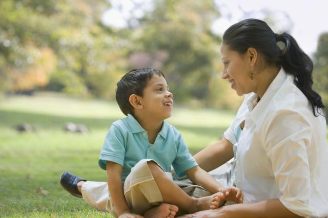 Hispanic mother and son smiling at each other