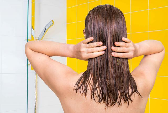 Attractive woman applying olive oil on her hair