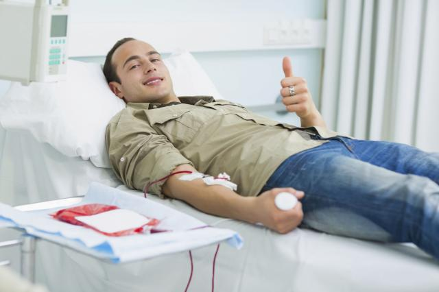 Smiling transfused patient lying on a bed