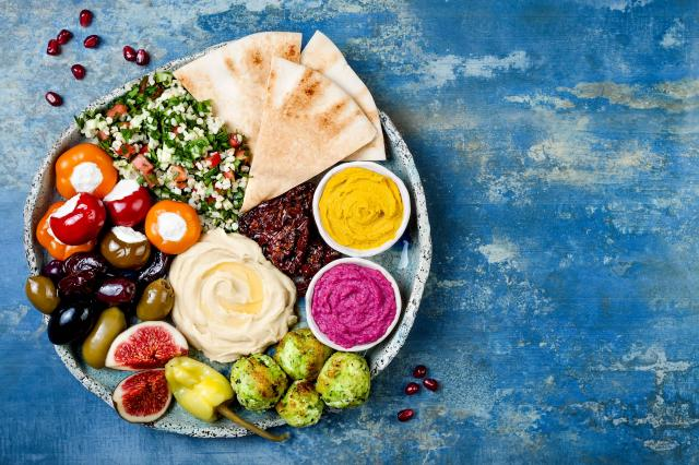 Middle Eastern meze platter with green falafel, pita, sun dried tomatoes, pumpkin and beet hummus, olives, stuffed peppers, tabb
