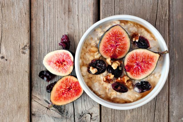 Oatmeal with figs, cranberries and walnuts over rustic wood