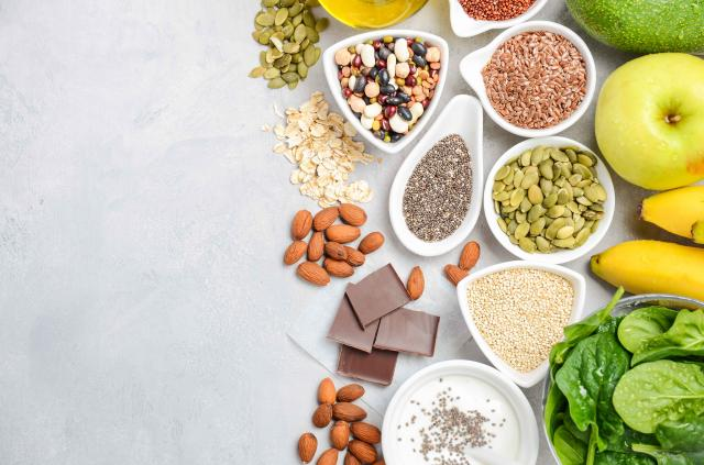 Healthy food nutrition dieting concept. Banana, chocolate, spinach, avocado, apple, quinoa, chia, flax seeds, yogurt, almond, be