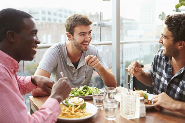 Three Male Friends Enjoying Lunch At Rooftop Restaurant