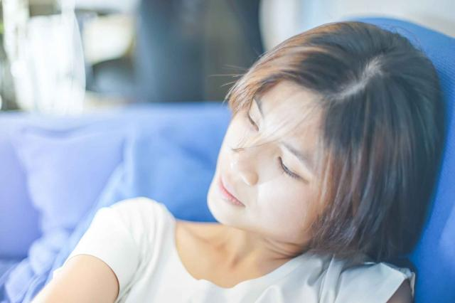 Tired Asian girl resting on a sofa.