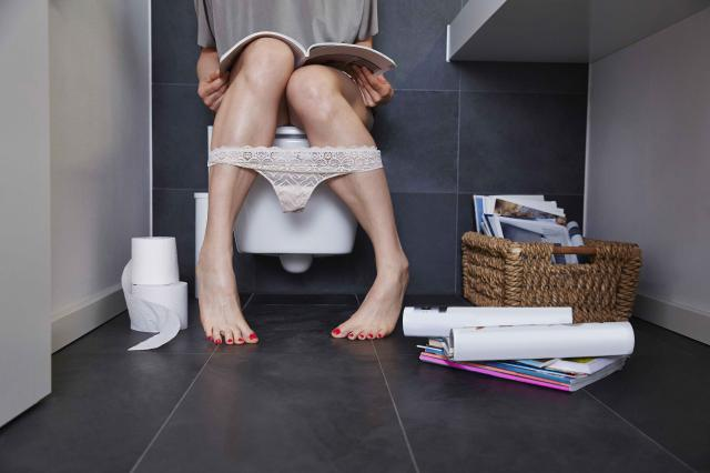 Woman reading on toilet with left-sided abdominal and back pain