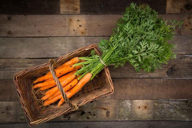 Bunch of carrots in basket, wood