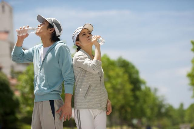 Couple drinking from water bottles