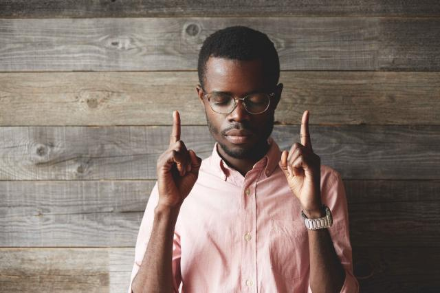 Portrait of handsome young African man, standing against wooden
