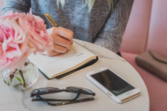 woman journaling at a cafe