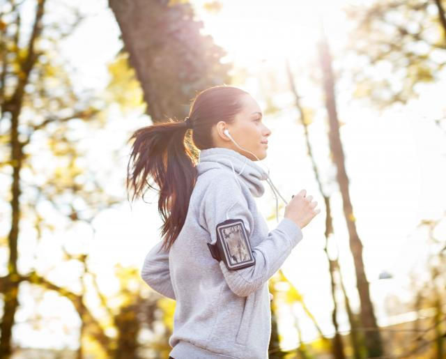 Sporty young woman running outside