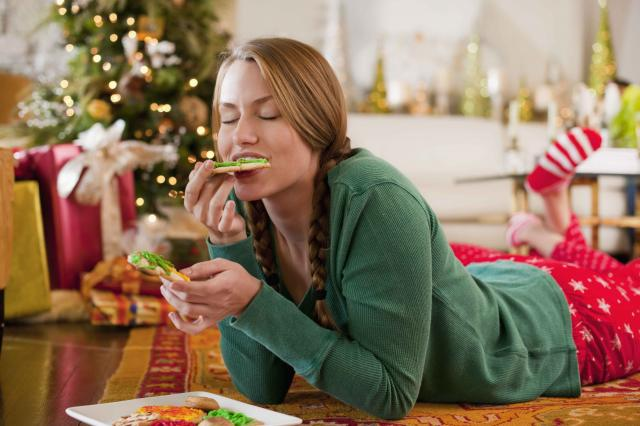 Caucasian woman eating Christmas cookies