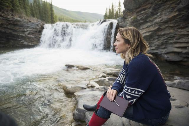 Pensive woman with journal at waterfall