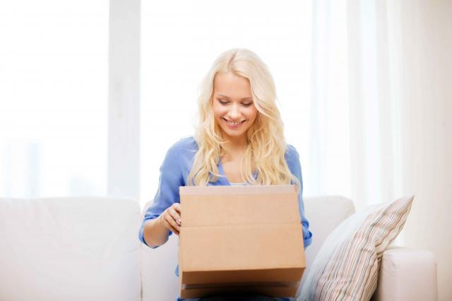 woman opening package containing monthly subscription box