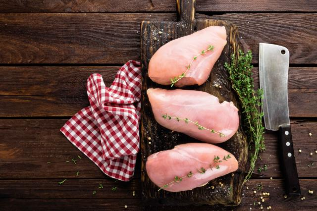Raw chicken breasts fillets with thyme and spices on wooden cutting board on rustic background, copy space, directly above