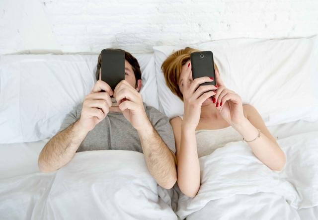 Couple laying in bed looking at their smart phones.