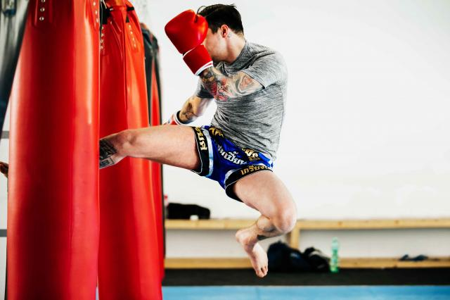 Kickboxer Performing Flying Kick On Punchbag