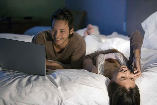 Asian couple relaxing on bed