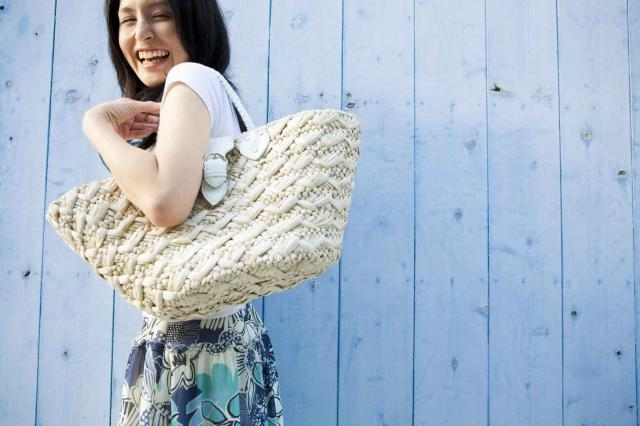 Woman with straw bag against blue wall