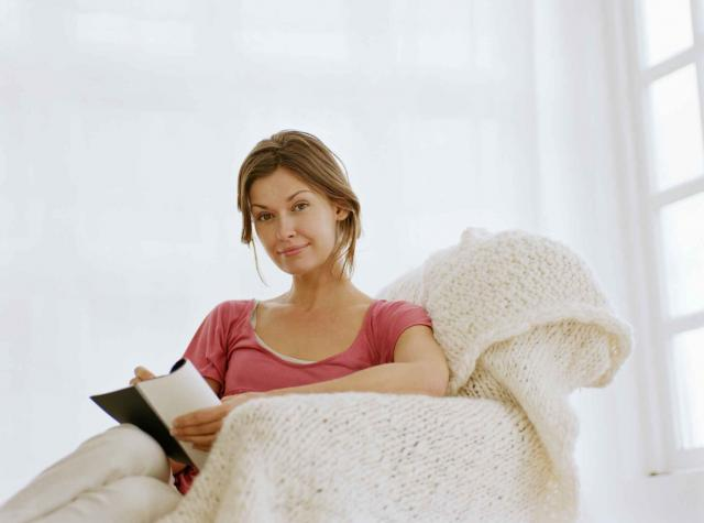 Woman relaxing in armchair holding pen and notebook, smiling