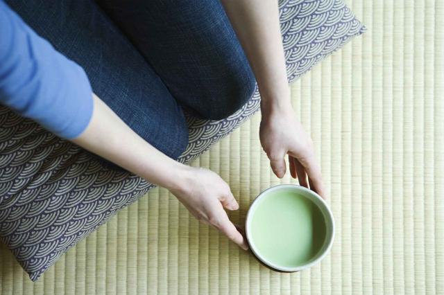 Woman holding bowl of green tea