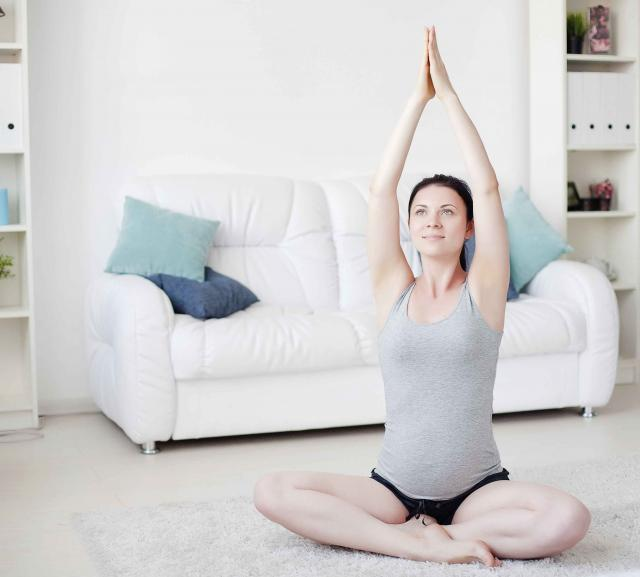 Young pregnant woman do yoga indoors