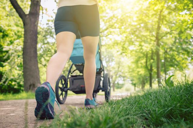 Walking woman with baby stroller enjoying summer in park