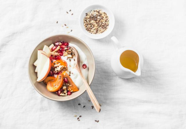 Full fruit and greek yogurt breakfast bowl. Persimmon, apple, walnuts, pomegranates and natural yogurt. Healthy food concept on
