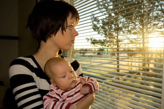 Young mother looking out from the window with her baby 2