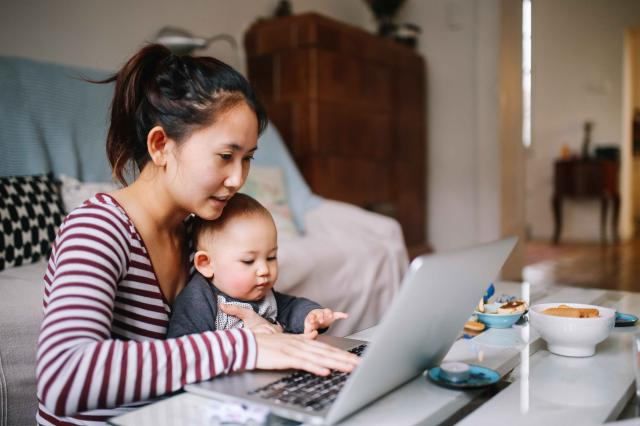 Young Asian mom trying to work with her baby boy