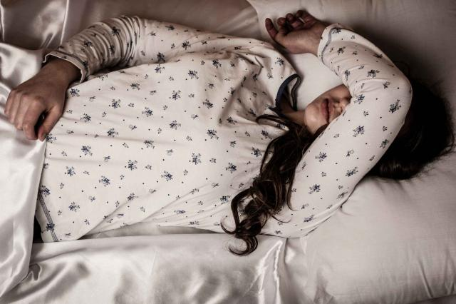 woman lying in bed with flu and fever feeling sick