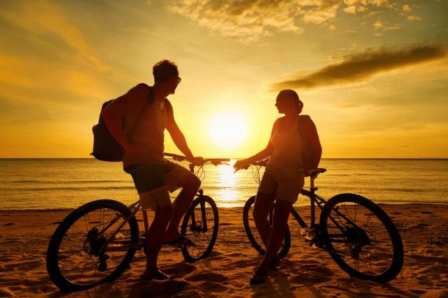 Couple tourists with Bicycles Watching Sunset. Silhouette people