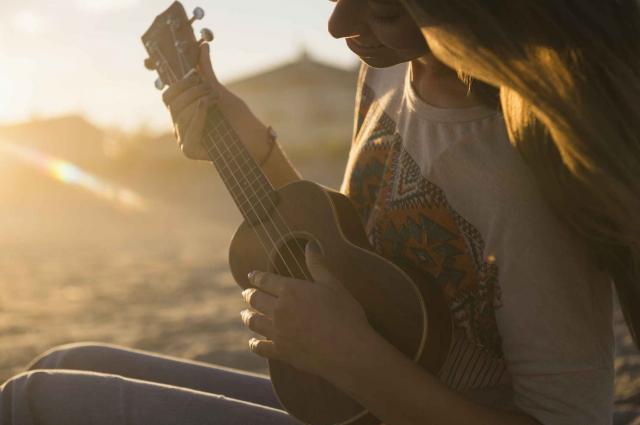 USA, New York State, Rockaway Beach, Woman playing ukulele at sunset