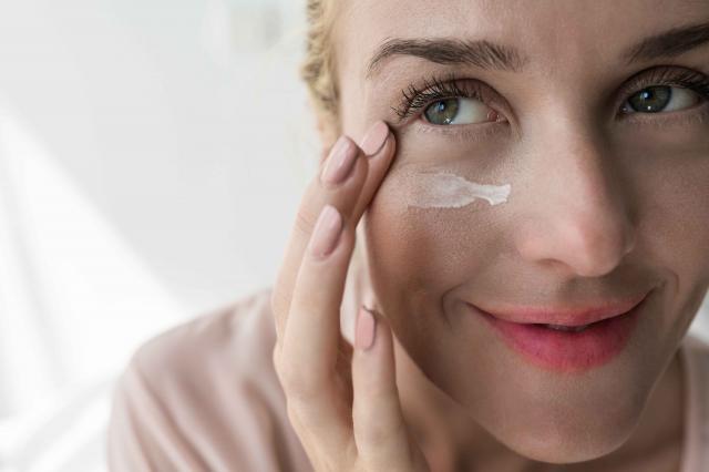 Woman Applying Creme Under Her Eye