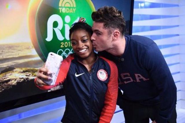 Simone Biles takes a selfie as Zac Efron kisses her cheek