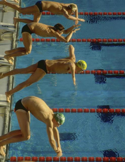 Swimmers diving into pool