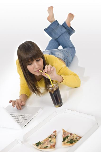 Happy female teenager with laptop lying down drink cola