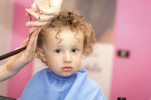 Hairdresser and toddler with curly hair