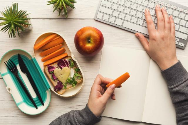 Woman eating healthy dinner from lunch box at her working table