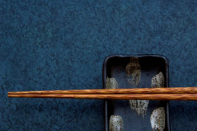 Chopsticks resting on small asian dish.