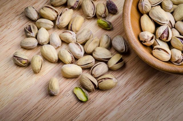 roasted and salted pistachios on wooden background..