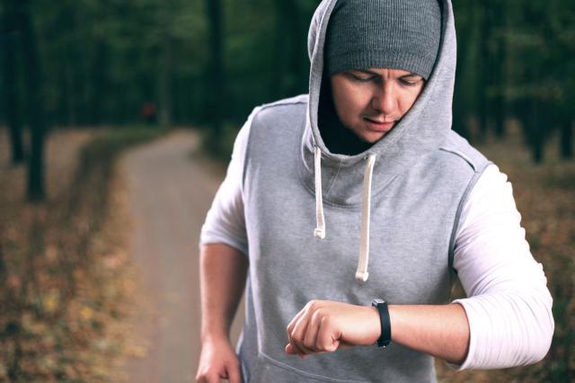 Urban runner woman reading wearable fitness tracker device
