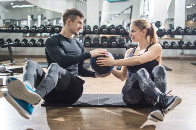 Sporty fitness couple doing abdominal exercises with medicine ball in the gym.