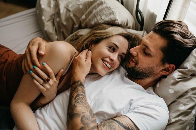 High Angle View Of Loving Young Couple Lying On Bed At Home